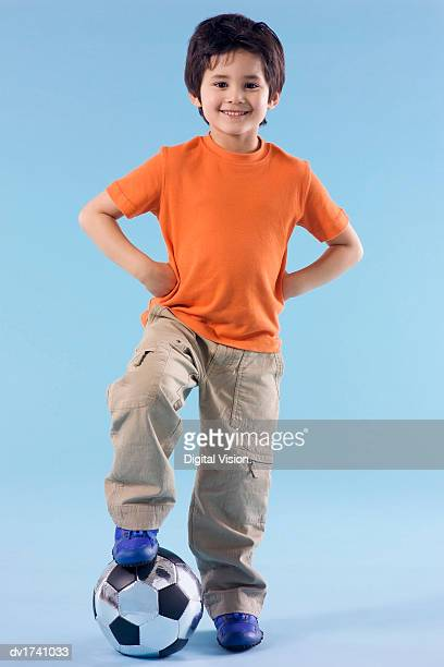 proud young boy standing with his foot on a football and his hands on his hips - arms akimbo stock pictures, royalty-free photos & images