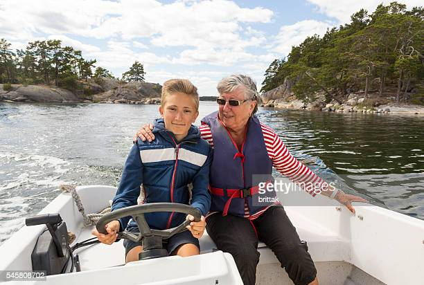 Proud young captain running small motor boat with grandmother.