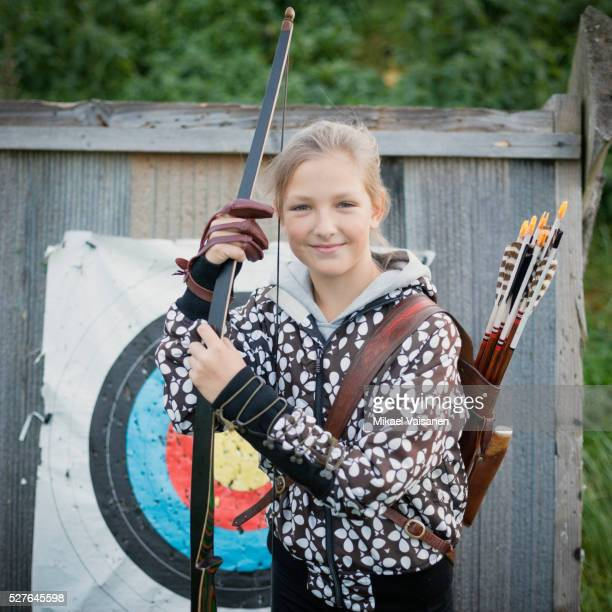 Proud young girl (10-12) posing with bow arrows in front of bull's eye