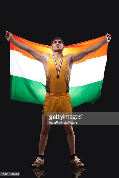 proud young medalist with indian flag standing against black background - medalist stock photos and pictures