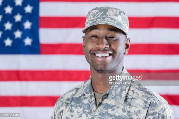 Proud young military man poses in front of American flag