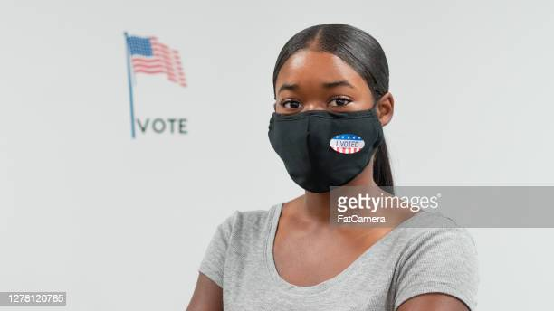 proud young woman posts by the american flag after voting - fatcamera stock pictures, royalty-free photos & images