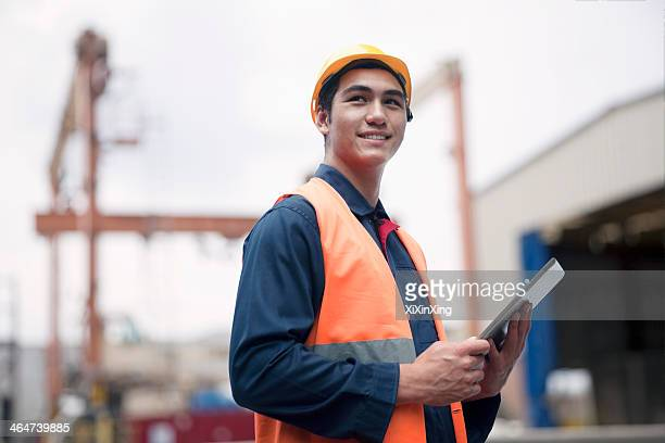 Proud young worker in protective work wear in a shipping yard