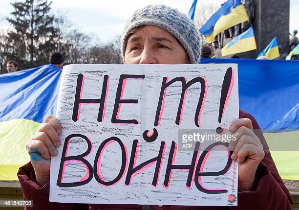 A ProUkrainian activist holds a placard reading 'No war' during a rally in front of the Shevchenko monument in the eastern Ukrainian city of Kharkiv...