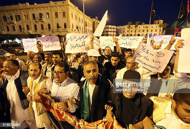 ProUNbacked government protesters hold placards and shout slogans during a demonstration in the Libyan capital Tripoli on April 1 2016 Hundreds of...