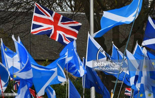 Pro-Union activists wave a Union flag as Scottish Saltire and EU flags fly during an anti-Conservative government, pro-Scottish independence, and...