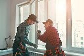 Provading best service. Men are installing a window