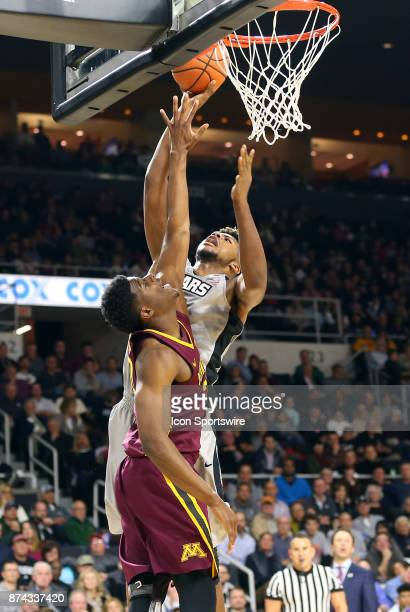 Providence Friars center Nate Watson shoots over Minnesota Golden Gophers forward Davonte Fitzgerald during a college basketball game between...