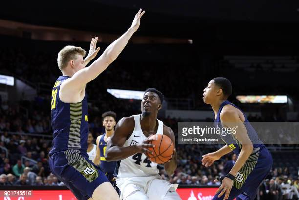 Providence Friars guard Isaiah Jackson defended by Marquette Golden Eagles center Harry Froling and Marquette Golden Eagles guard Greg Elliott during...