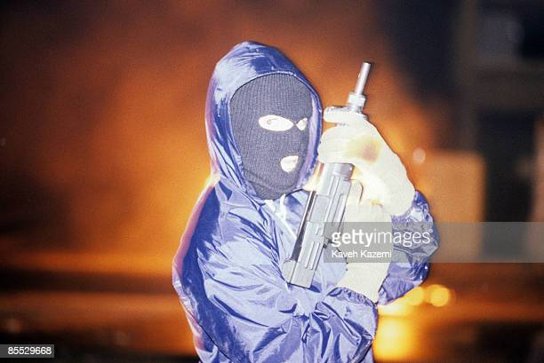 A Provisional IRA gunman stands with his automatic assault rifle and a mask after having hijacked and set ablaze a bus on the eve of Apprentice Boys...