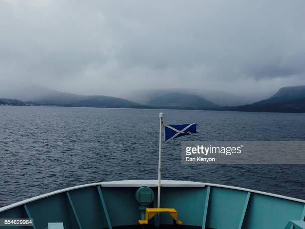 Prow of ferry approaching Isle of Arran with Scottish flag