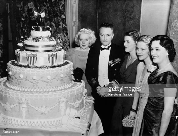 Près du grand gâteau d'anniversaire, de gauche à droite, Alice Faye, l'amiral Byrd, Betty Furness, Glenda Farrell et Sue Gomez, à Los Angeles,...