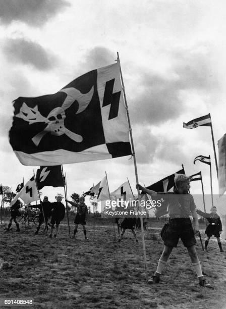 Présentation des drapeaux lors d'un rassemblement des Jeunesses Hitlériennes en juin 1935 en Allemagne