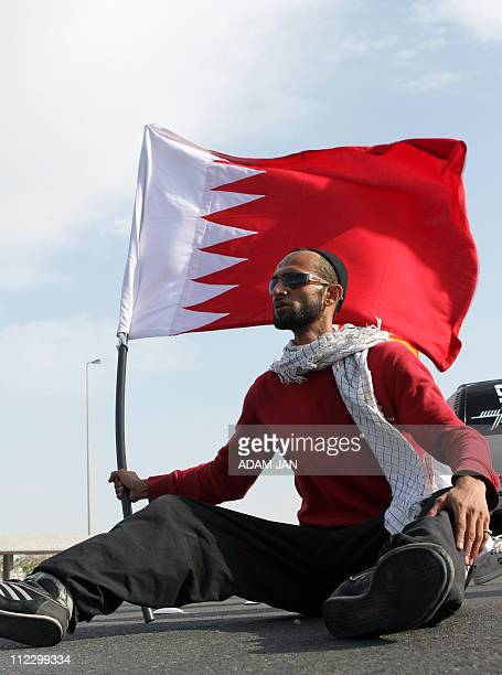Prtoester sits on the road as thousands of Bahraini Shiite anti-government demonstrators march toward the royal palace in Manama on March 11, 2011...