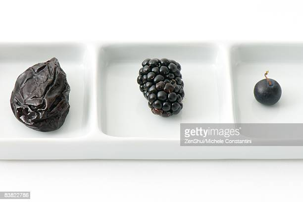 Prune, blackberry and blueberry on dish with compartments