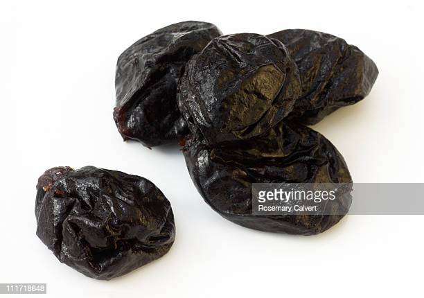 Prunes in a pile with one prune beside pile.