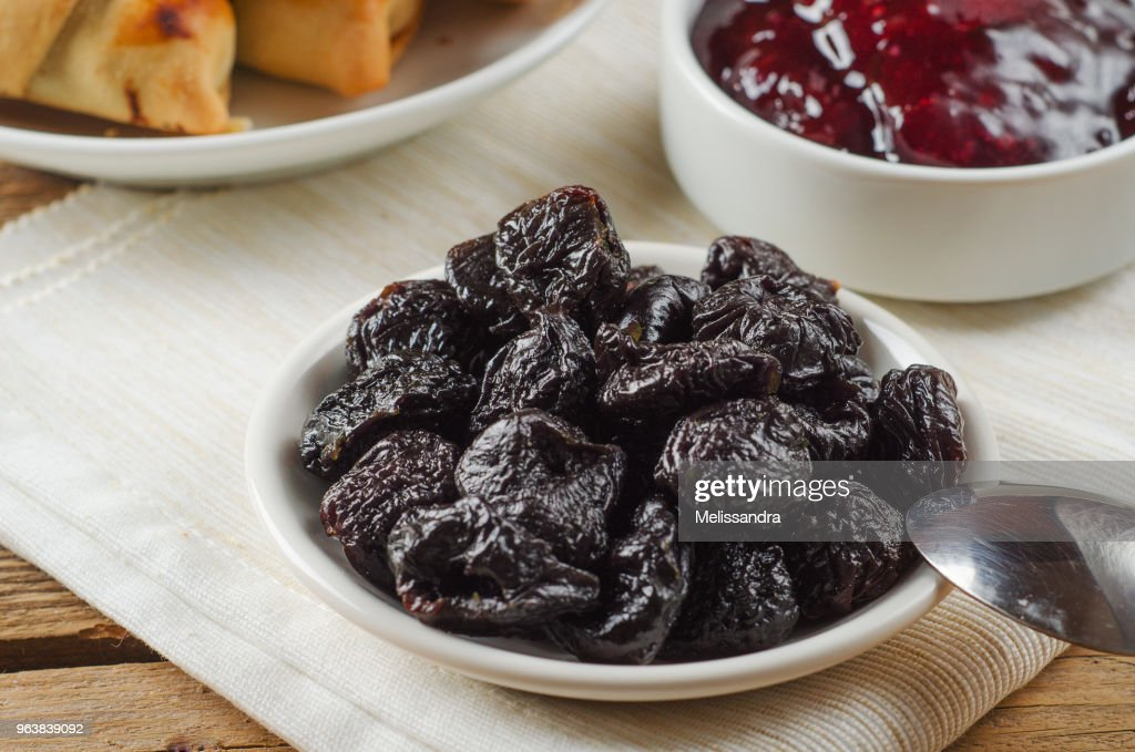 Prunes on small plate with jam from the plums on wooden table. Dried Plums. Healthy and vegetarian food : Stock Photo