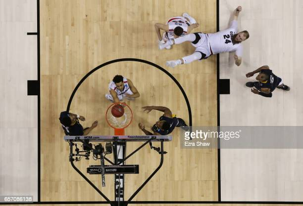 Przemek Karnowski falls to the court as Josh Perkins of the Gonzaga Bulldogs looks for a rebound against the West Virginia Mountaineers during the...