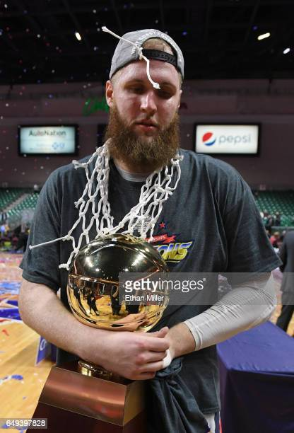 Przemek Karnowski of the Gonzaga Bulldogs carries the trophy off the court following the team's 7456 victory over the Saint Mary's Gaels to win the...