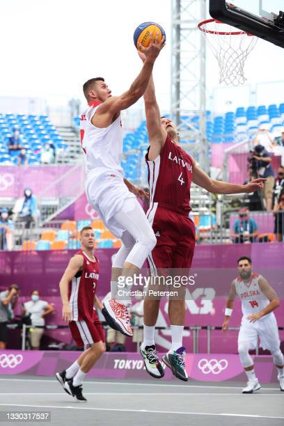 Przemyslaw Zamojski of Team Poland drives to the basket under pressure from Agnis Cavars of Team Latvia during the Men's Pool Round match between...