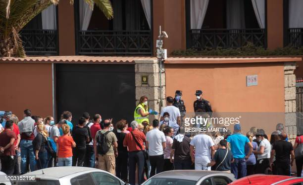 Psychologist talks to a group of workers outside the H10 Costa Adeje Palace Hotel in La Caleta, on February 25 where hundreds of people were confined...