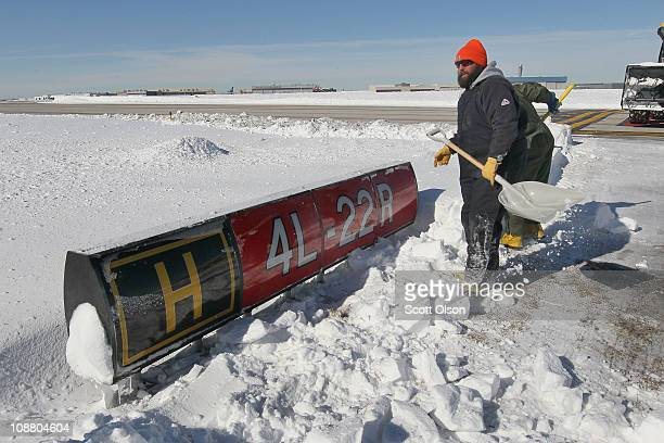 Ptrick Nolan clears snow from a runway sign at O'Hare International Airport February 3 2011 in Chicago Illinois Commercial carriers at the airport...