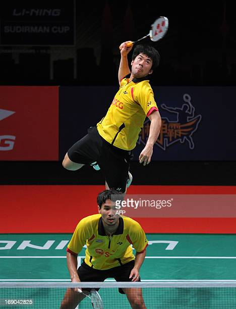 Puangpuapech Nipitphon of Thailand jumps to hit a smash as teammate Jongjit Maneepong looks on during their match against Hong Kong at the 2013...