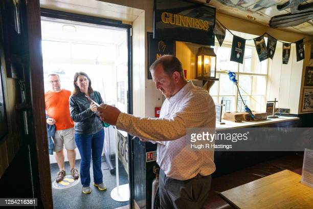Pub Manager Nathan Boundy welcomes customers at the Chain Locker pub as it reopens for business on July 4 2020 in Falmouth Cornwall United Kingdom...