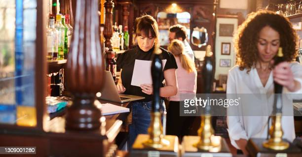 pub owner dealing with accounts - pub stock pictures, royalty-free photos & images