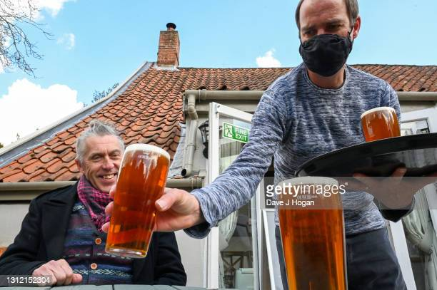 Pub regular has his first pint of beer following lockdown in the beer garden of the Queen Head public house on April 12, 2021 in Halesworth, England....