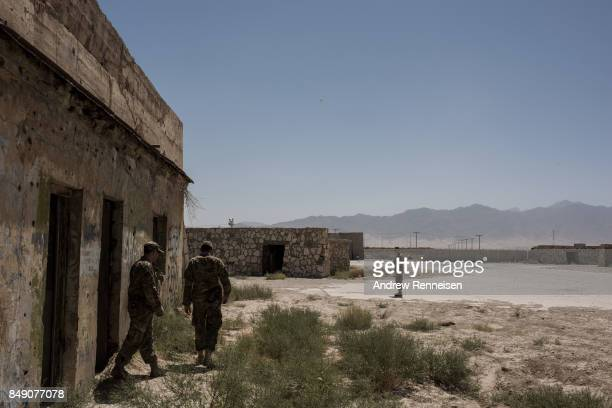 Public Affairs Officers with the United States Air Force deployed for Mission Resolute Support walk around building in ruins at Bagram Air Field on...