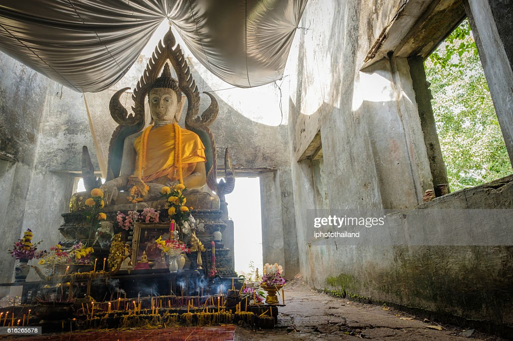 Public ancient Thai Buddha statue left in the forest : Stock Photo