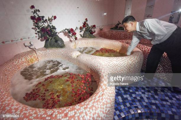 A public bathhouse staffer checks a bathtub filled with flower petals in Pyongyang on June 14 2018 ==Kyodo