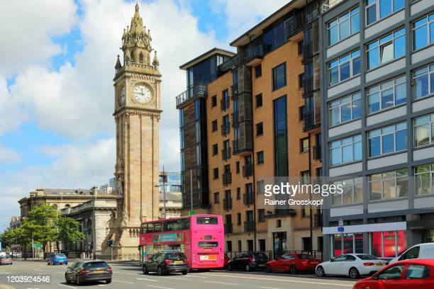 a public bus driving along victoria street to albert memorial clock tower in belfast - rainer grosskopf stock pictures, royalty-free photos & images
