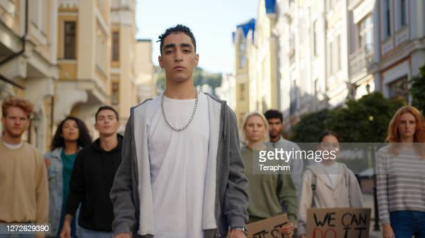 public demonstration at city street with hispanic man in front of multiracial protesting people - campaigner stock pictures, royalty-free photos & images