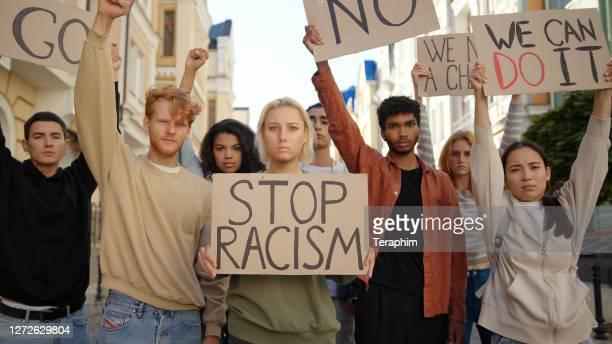 offentlig demonstration på gatan mot rasism med slagord på affischer. multietniska människor protesterar - etnicitet bildbanksfoton och bilder