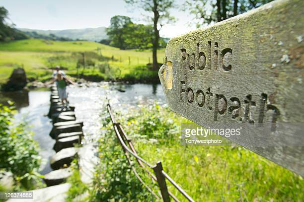 Public footpath sign pointing to river with stepping stone showing