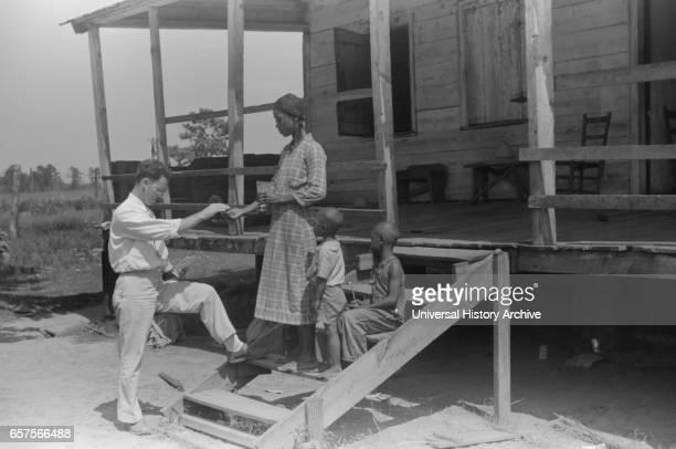 Public Health Doctor giving Tenant Family Medicine for Malaria, near Columbia, South Carolina, USA, Marion Post Wolcott for Farm Security...