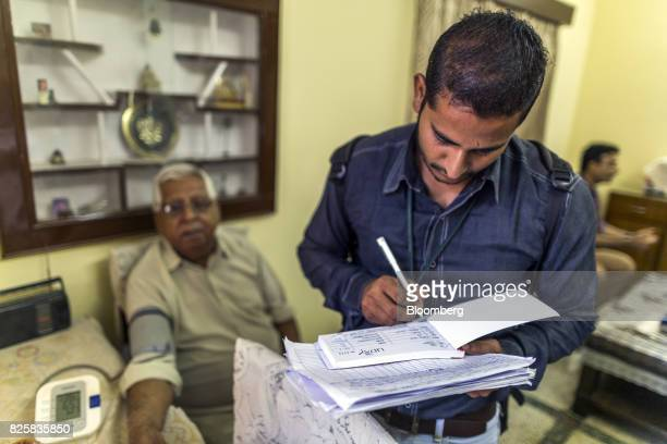 A Public Health Foundation of India worker prepares a report for a patient during a free doortodoor screening program funded by Eli Lilly Co at a...