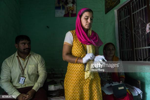 A Public Health Foundation of India worker puts on a pair of rubber gloves during a free doortodoor screening program funded by Eli Lilly Co at a...