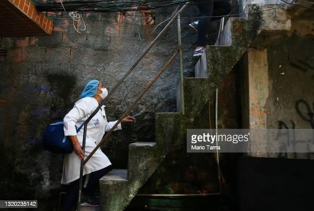 Public health nurse Lucia Maria Sousa ascends a staircase to administer a COVID-19 vaccination dose to a homebound resident in the Rocinha favela...