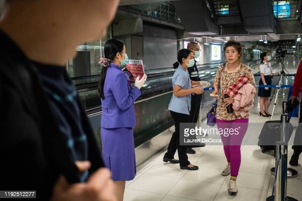 Public Health Officials hand out disease monitoring information after performing a thermal scans on passengers arriving from Wuhan China at...