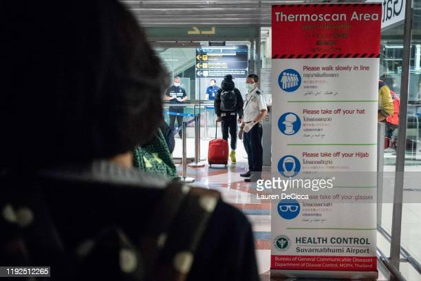 Public Health Officials run thermal scans on passengers arriving from Wuhan China at Suvarnabumi Airport on January 8 2020 in Bangkok Thailand...