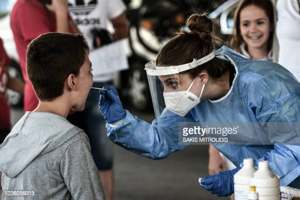 Public health worker collects a swab sample from a boy to test for the COVID-19, the novel coronavirus, at the Greek-Bulgarian border crossing in...