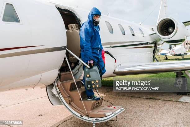 a public health worker in blue protective suit and a mask exiting a small business plane - department of health stock pictures, royalty-free photos & images