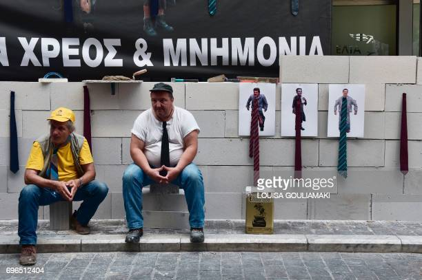 TOPSHOT Public hospitals' health workers wearing a tie sit by a wall they built in front of the Finance ministry in Athens next to a banner reading...