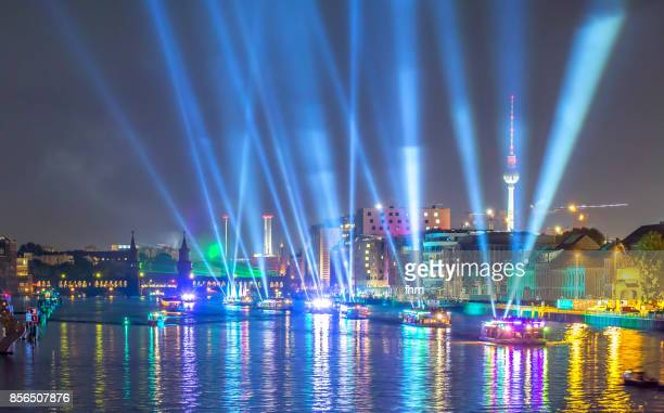 Public light event in Berlin - light beams at the Berlin skyline with landmarks molecule men, Oberbaumbrücke and Televisiontower (Berlin, Germany)