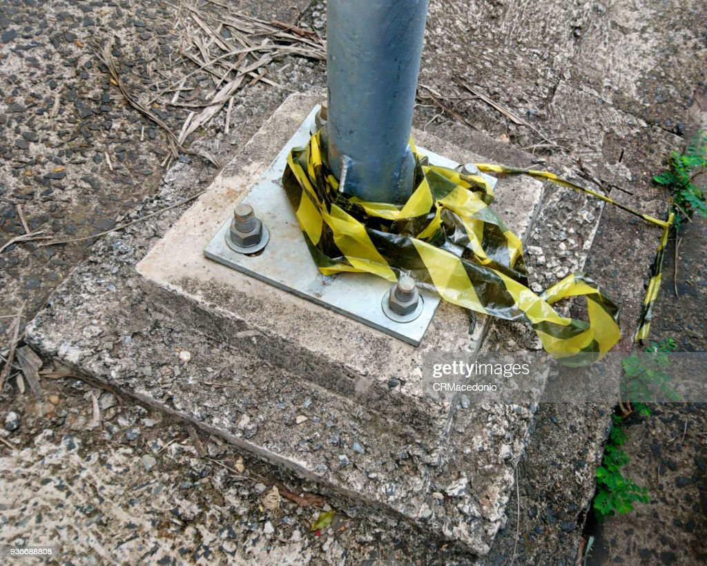 Public light pole base, fixed to the floor with screws, and remnants of signaling tape. : Stock Photo