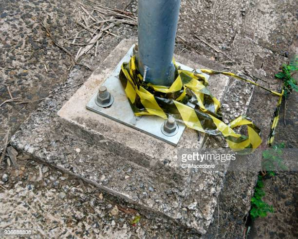 public light pole base, fixed to the floor with screws, and remnants of signaling tape. - crmacedonio stock-fotos und bilder
