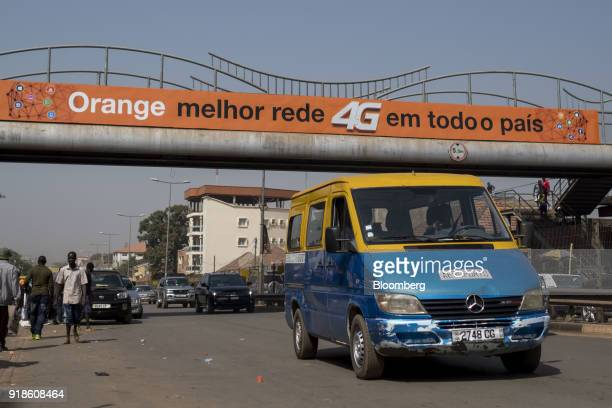 A public minibus known locally as 'tocatoca' drives under an Orange Bissau SA advertisment in Bissau GuineaBissau on Monday Feb 12 2018 The...